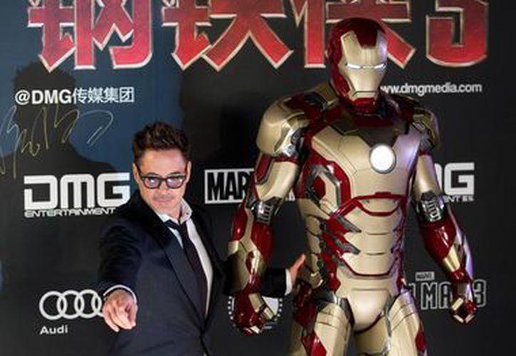 """El actor Robert Downey Jr. posa junto al traje de """"Iron Man"""" en la conferencia de prensa en Beijing, (Agencias)"""