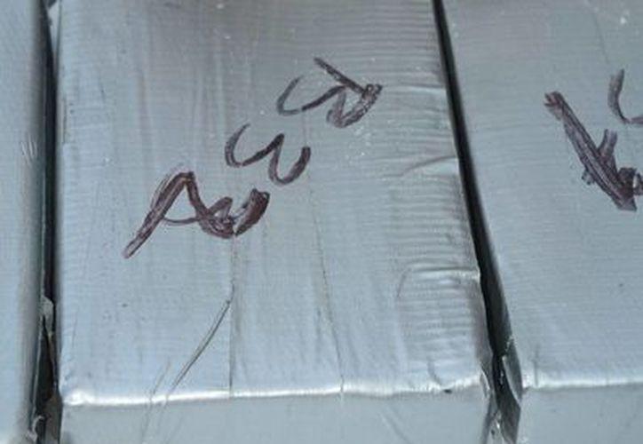 El cargamento estaba oculto en el fondo de una embarcación pesquera de 10 metros de eslora frente a costas de Santo Domingo. Imagen de unos paquetes de cocaína al ser analizados por un agente. (Archivo/Notimex)