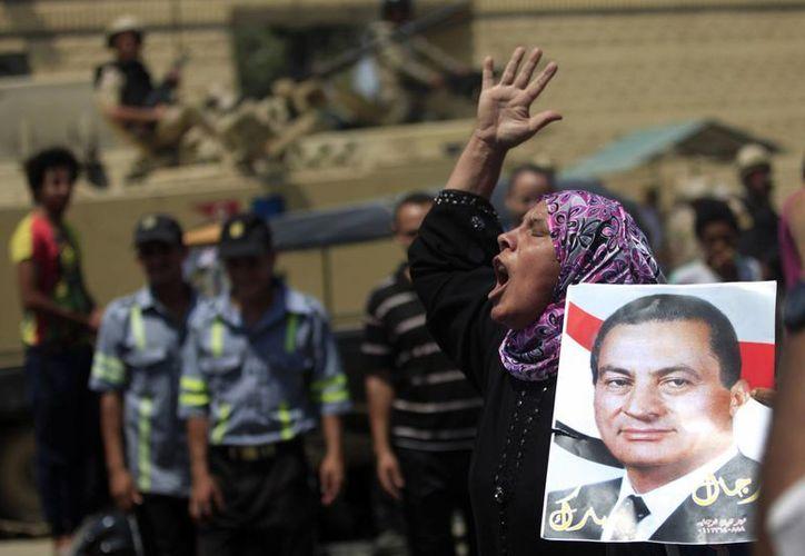 Simpatizantes de Mubarak sostienen posters y otros artículos en relación al expresidente egipcio, a las afuera de la prisión de Torah, de donde ya salió. (Agencias)