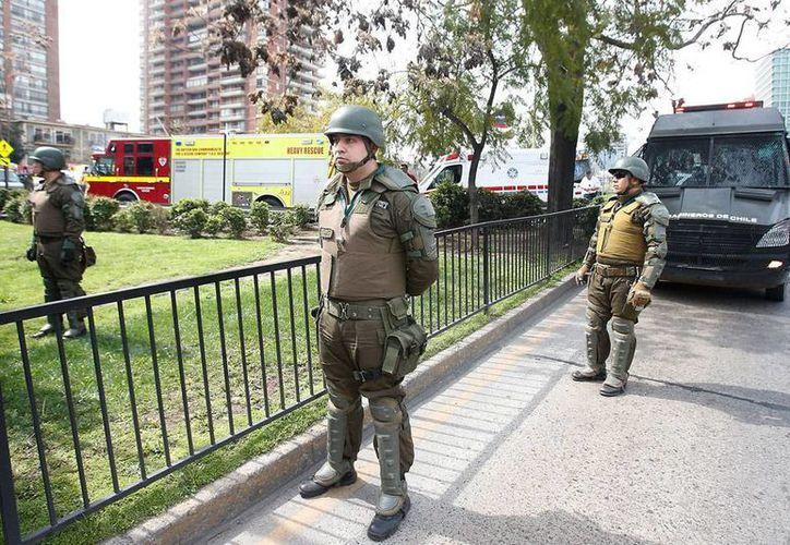 Policías montan guardia a las afueras de la estación del metro 'Escuela Militar, en Chile, donde el pasado 8 de septiembre estalló un artefacto explosivo que dejó como saldo varios heridos. Este jueves, las autoridades detuvieron a 3 sospechosos. (Archivo/Efe)