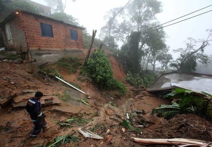 Un rescatista inspecciona la zona de un deslizamiento provocado por las fuertes lluvias que afectan Petrópolis, Río de Janeiro. (EFE)