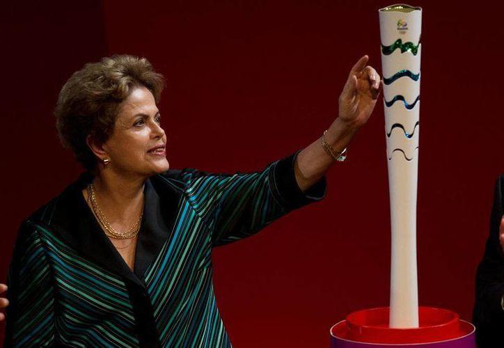 La presidenta de Brasil, Dilma Rousseff, junto a la antorcha olímpica que se utilizará en Río 2016, la cual recorrerá este país del tres de mayo al cinco de agosto, día en que inician los Juegos Olímpicos. (AP)