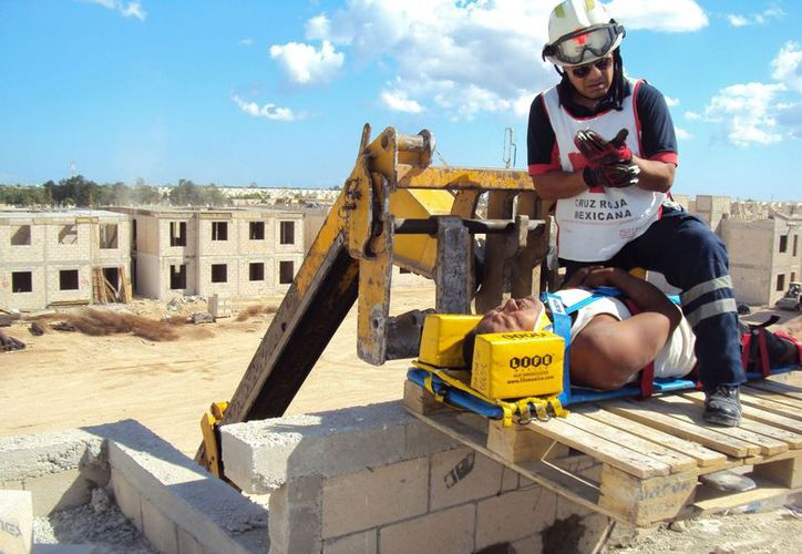 Los paramédicos de la Cruz Roja tuvieron que subir al techo de la construcción para bajar al albañil. (Juan Estrada/SIPSE)