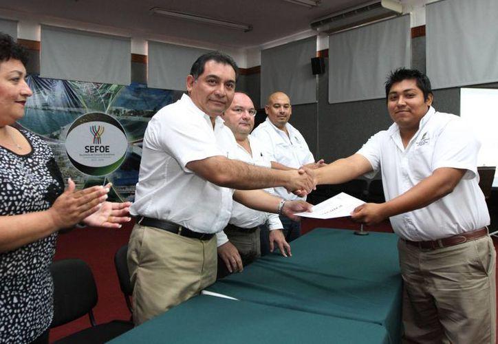 El secretario general de Gobierno, Víctor Caballero Durán, entrega constancia de capacitación a un inspector de transporte público. (SIPSE)