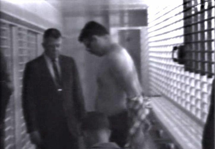 En otro momento del video, se observa cuando la policía desnuda al asesino, mientras lo revisa un médico. (Agencias)