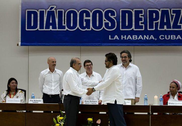 En esta fotografía tomada el 15 de diciembre de 2015 el jefe negociador del gobierno colombiano, Humberto de la Calle, (adelante, a la izquierda), le da la mano a Iván Márquez, jefe negociador de las FARC, tras la firma de un acuerdo sobre como reparar a millones de víctimas del conflicto colombiano. (Agencias)
