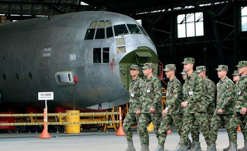 Miembros de la Fuerza Aérea Colombiana pasan en frente de un avión Hércules en proceso de mantenimiento en la Base Aérea Justino Mariño Cuesto, situada en el municipio de Madrid, Cundinamarca. (COLOMBIA.INN)