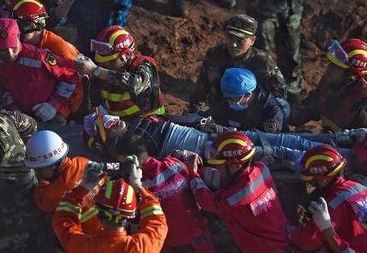 Un sobreviviente es hallado en medio de las ruinas tras el alud en un parque industrial en Shenzhen, en el sur de China 67 horas después de un alud (AP)