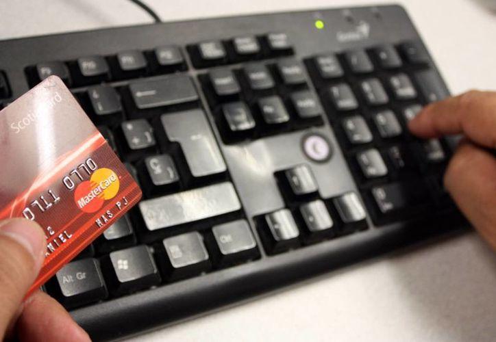 Las personas afectadas por el robo de datos de algún banco, deben acudir al Ministerio Público a presentar la denuncia correspondiente. Imagen de contexto de un hombre con su tarjeta de crédito al ingresar su número de cuenta a la red. (Archivo/SIPSE)