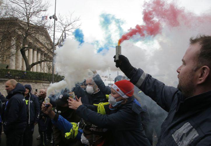 Trabajadores de ambulancias encienden bengalas en el exterior de la Asamblea Nacional francesa. (AP)