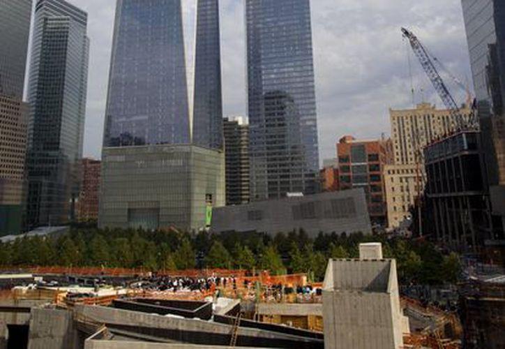 En esta imagen de archivo del 18 de octubre de 2014, el One World Trade Center de fondo mientras la gente se reúne, abajo, para una ceremonia en el altar de San Nicolás, en Nueva York. (Agencias)