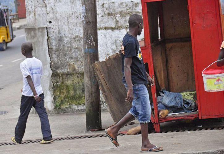 Dos hombres caminan junto a una caseta donde yace el cadáver de un tercero (derecha), muerto posiblemente por ébola, en una de las calles más transitadas de Monrovia, Liberia. (Agencias)