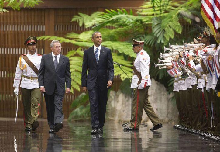 Los presidentes Raúl Castro y Barack Obama caminan durante una ceremonia de bienvenida en el Palacio de la Revolución. (Agencias)