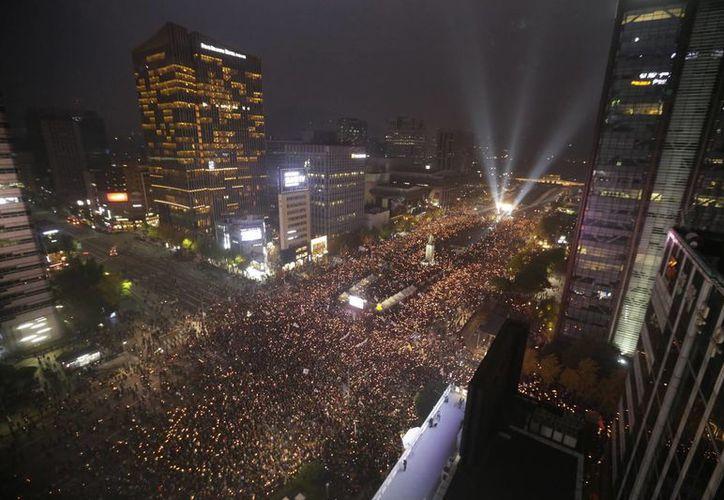 Miles de manifestantes participan en una protesta para exigir la renuncia de la presidenta Park Geun-hye, en el centro de Seúl, Corea del Sur. (AP/Ahn Young-joon)