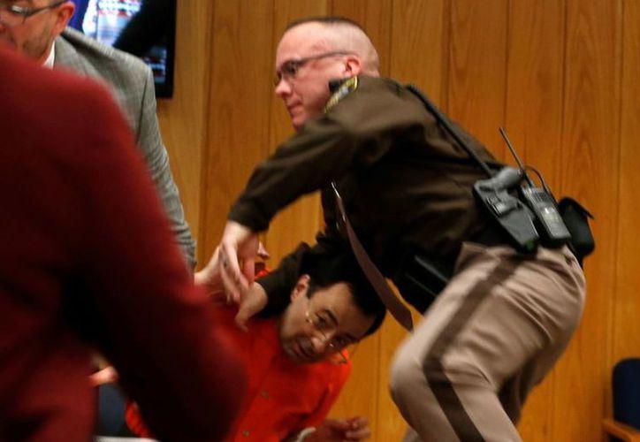 El padre de una de las víctimas de Larry Nassar, se lanzó sobre él para agredirlo, pero fue detenido. (Foto: Twitter)