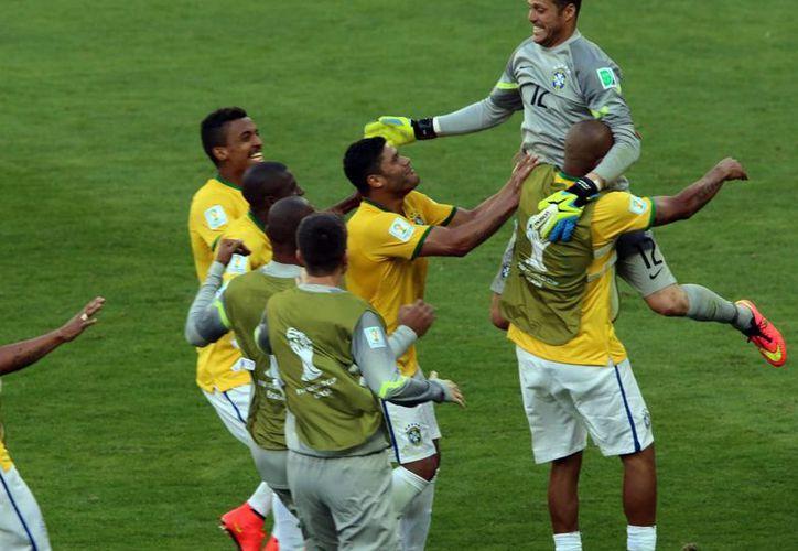 Julio César (d) en un momento alegre con Brasil, que luego fue goleado 7-1 por Alemania en la semifinal del Mundial. (Notimex/Foto de archivo)