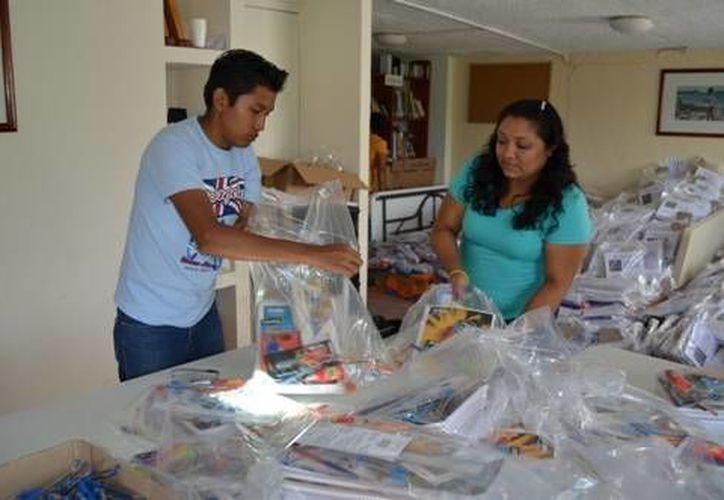 Representantes de la Fundación Cozumel y el Nacional Monte de Piedad preparan los paquetes de útiles escolares que a partir de la próxima semana podrán recoger más de mil estudiantes. (Redacción/SIPSE)
