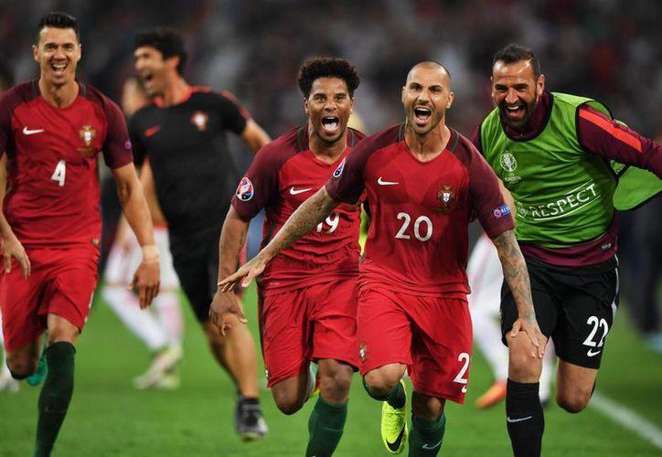 Portugal anotó sus cinco penales y calificó a semifinales de la Eurocopa luego de haber empatado 1-1 con Polonia. En la foto Quaresma (2-d) celebra el quinto penal anotado. (EFE)