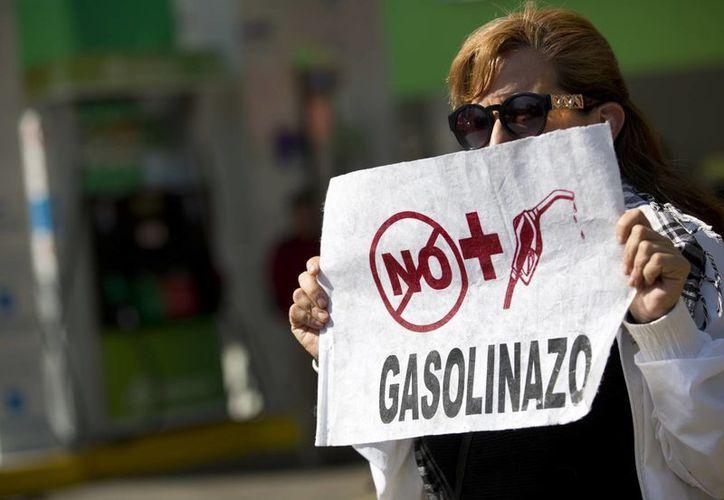 Necesitamos una estrategia entre la sociedad y el gobierno para combatir la inflación, promover la inversión y defender el empleo: CCE. Imagen de contexto de una mujer que se manifiesta en contra del 'gasolinazo'. (AP Photo/Rebecca Blackwell)