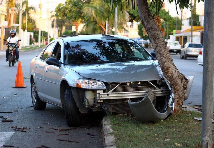 Imagen de un vehículo Stratus que se estrelló contra un árbol por evitar chocar contra otro vehículo que se pasó el alto. (Milenio Novedades)