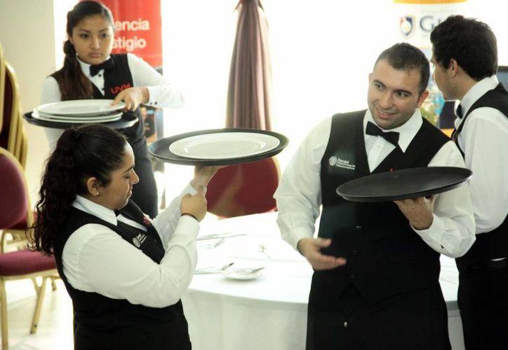 A partir de octubre habrá una sola zona salarial en el país. Imagen de un grupo de empleados del sector turístico. (Milenio Novedades)
