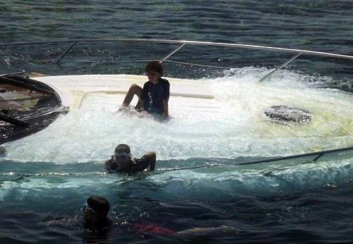Niños juegan sobre el yate encallado en Arrecife Alacranes. (Milenio Novedades)