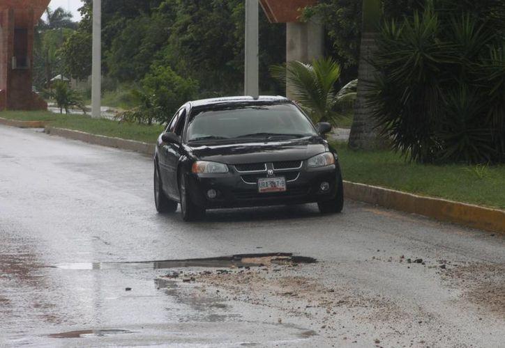 Los encharcamientos por las lluvias cubren los baches y provocan accidentes. (Harold Alcocer/SIPSE)