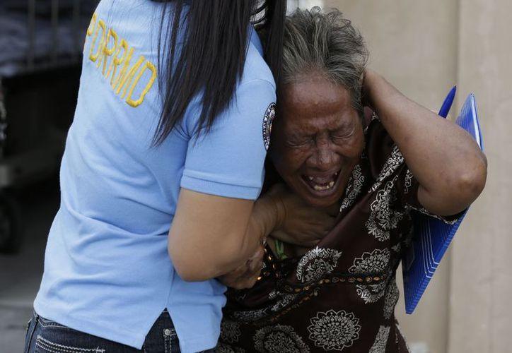 Una mujer llora tras reconocer a un familiar víctima del tiroteo. (Agencias)