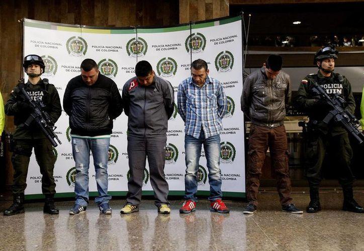 """Miembros de la Policía custodian a cuatro de los seis presuntos responsables del homicidio del agente James """"Terry"""" Watson. (EFE)"""