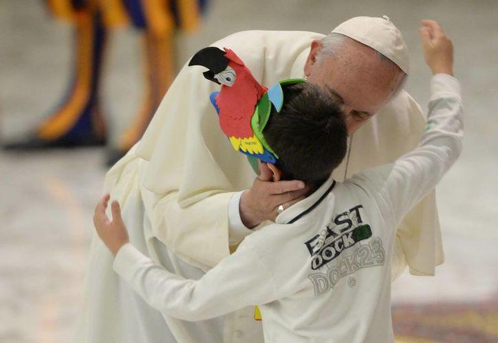 El Papa Francisco besa a un niño durante una audiencia en el Aula Pablo VI del Vaticano. (EFE)