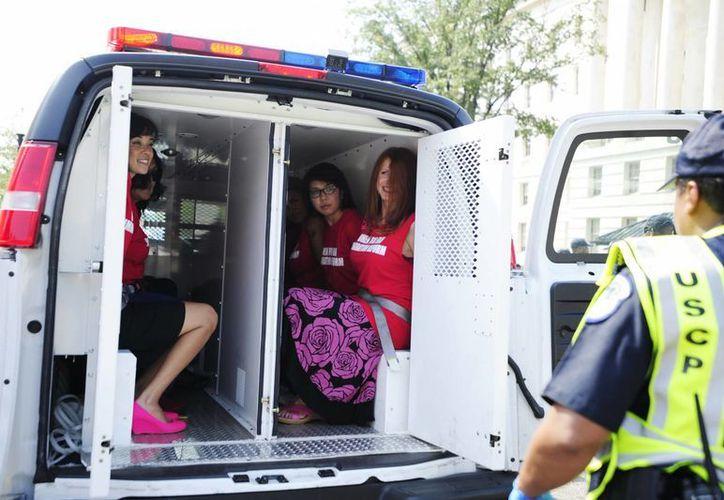 Sin resistirse al arresto, las mujeres fueron escoltadas a camiones de la policía. (Agencias)