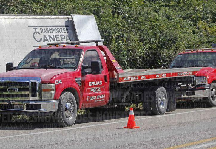 Las empresas de grúas intentaron rescatar un tráiler en el kilómetro 259 de la autopista Valladolid-Cancún. (Jesús Tijerina/SIPSE)