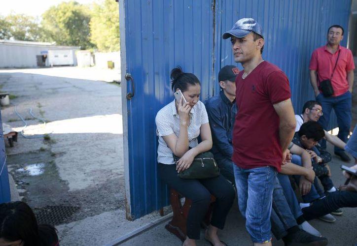 Colegas y familiares de los trabajadores muertos de Kirguizistán se reunieron cerca del edificio quemado donde se alojaba una imprenta en Moscú, Rusia. (Foto AP / Ivan Sekretarev)