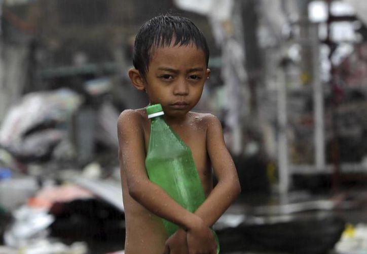 En la imagen del mes de noviembre, un niño sosteniendo una botella de agua bajo la lluvia en la devastada ciudad de Tacloban, Filipinas. (EFE)