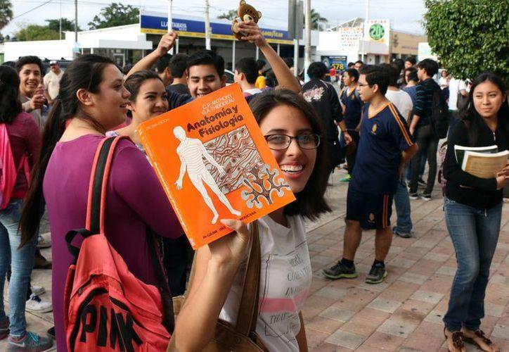 La venta de libros usados, buen negocio para algunos. Imagen de una joven que ofrece un material didatico al mejor postor. (Milenio Novedades)