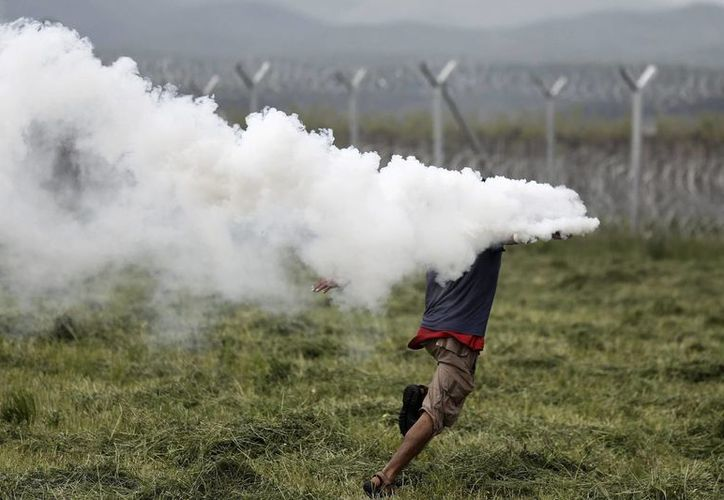 Un refugiado lanza de vuelta un bote de gas lacrimógeno durante una protesta en el campo de refugiados de Idomeni, situado en la frontera entre Macedonia y Grecia. (EFE)