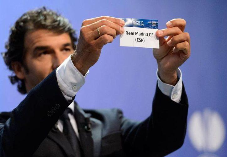 El exjugador Karl-Heinz Riedle, embajador de UEFA Champions League,    muestra el papel que contiene en el nombre del Real Madrid, durante el sorteo de partidos de semifinal de la Liga de Campeones. (AP)