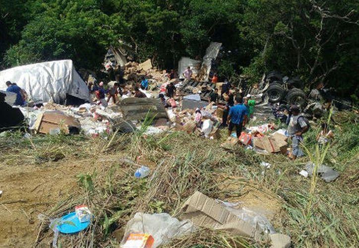 Los automovilistas que circulaban por la carretera y algunos pobladores cercanos, bajaron hasta donde quedó el vehículo en el barranco y comenzaron a llevarse los víveres. (Abraham Jiménez López/Milenio)