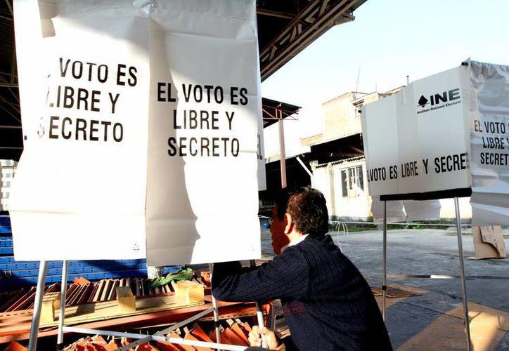 Imagen de un funcionario electoral al momento de instalar una de las casillas en la Ciudad de México. (Notimex)