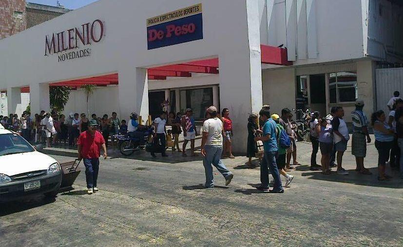 Cientos de personas aguardan un autobús para llegar al puerto de Progreso. (Francisco Pantoja/SIPSE)