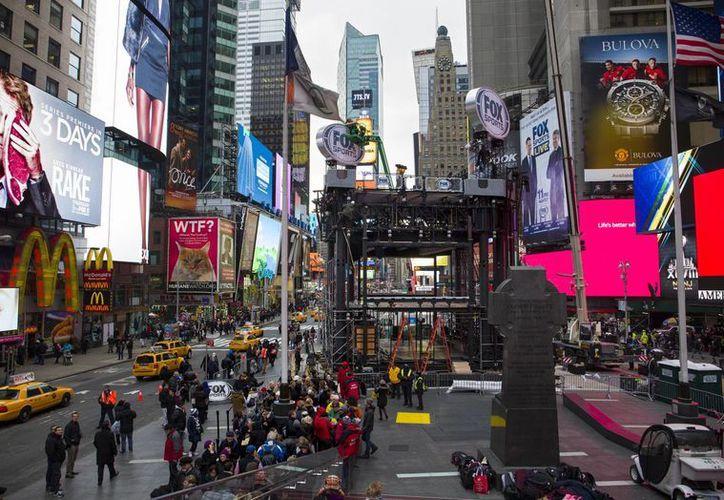 Trabajadores construyen un andamio para una cadena televisiva en Times Square, previo al Super Bowl. (Agencias)