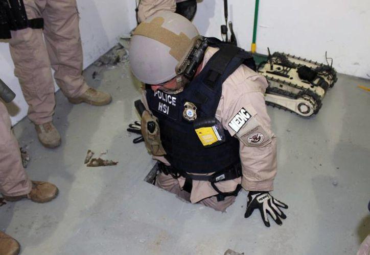 Fotografía proporcionada por la Policía de Inmigración y Aduanas que muestra a un agente examinando uno de dos túneles descubiertos en el condado de San Diego, el martes 1 de abril de 2014, en un parque industrial de Otay Mesa. (Foto AP/ ICE)