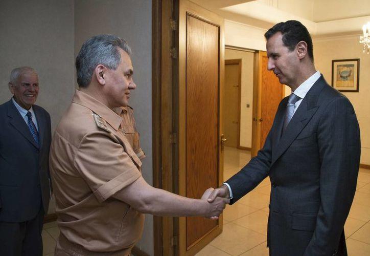 Fotografía de archivo del presidente sirio Bashar Assad (der) estrechando la mano del ministro ruso de la Defensa Sergei Shoigu en Damasco, Siria. (Vadim Savitsky/Ministerio ruso de la Defensa, fotografía de pool vía AP)