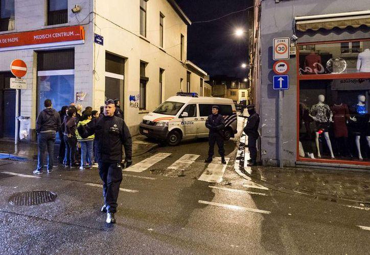 Policías vigilan una calle en el vecindario Molenbeek en Bruselas, Bélgica, país que ha reforzado la seguridad en sus ciudades importantes, luego de que se informara que los ataques del viernes en París, Francia, fueron en parte organizados desde Bélgica. (AP)