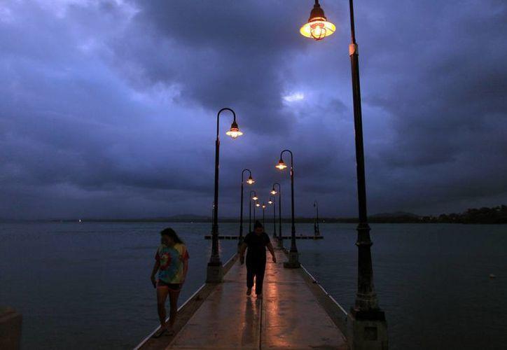 Una pareja camina por un muelle mientras la tormenta tropical Erika se acerca a la isla en Naguabo, Puerto Rico. (Agencias)