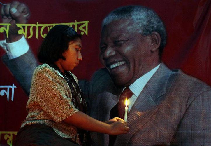 Una niña sostiene una vela mientras se reza por la recuperación del expresidente sudafricano Nelson Mandela en Dhaka, Bangladesh. (Agencias)