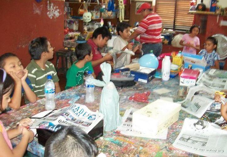 Niños se divierten en el taller de reciclaje, en donde realizan manualidades. (Redacción/SIPSE)