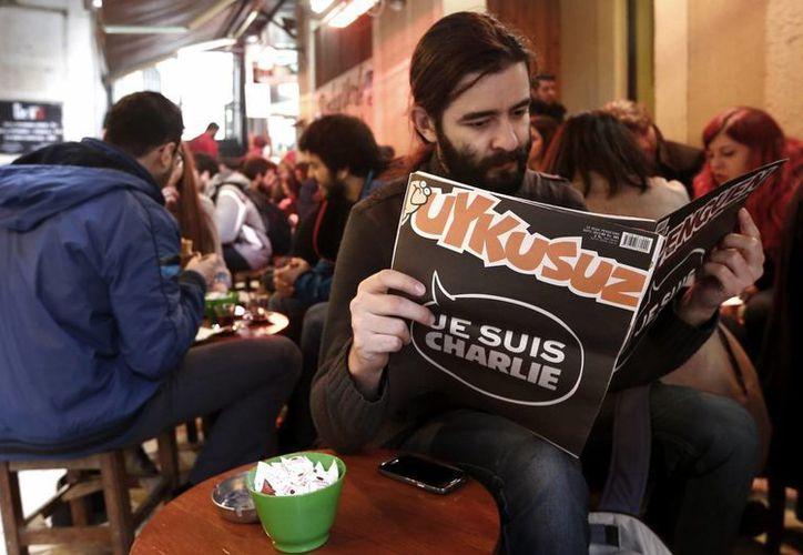 """Un hombre lee ayer la edición de la revista turca satírica Uykusuz en Estambul, que ha publicado en su portada """"Je suis Charlie"""" en homenaje a la revista francesa Charlie Hebdo. (Foto EFE)"""
