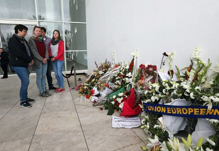Visitantes extranjeros observan las ofrendas a las afueras del museo del Bardo, en Túnez, donde el mes pasado 21 turistas murieron, en un atentado terrorista. (Archivo/Efe)