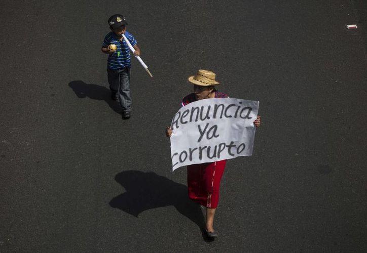 Una mujer participa en una marcha en Guatemala para pedir la salida del poder de Otto Pérez Molina, este 27 de agosto de 2015. En un giro sorprendente, la Procuraduría General de la Nación pidió al Mandatario que presente su renuncia. (AP Foto/Moisés Castillo, Archivo)